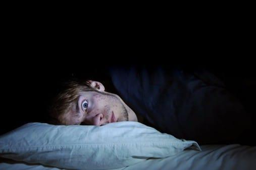 sleeplessness man lying awake at night image