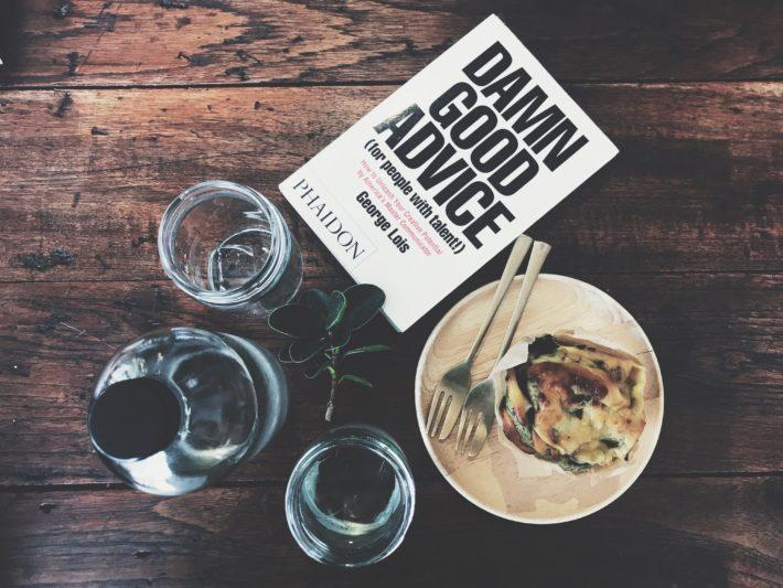 A meal with glasses of water and a book titles Damn Good Advice