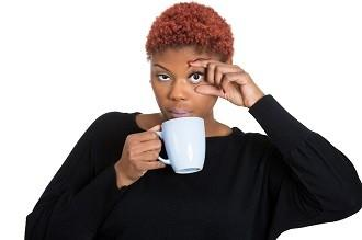 lifespa image, tired woman holding eye open while holding coffee cup