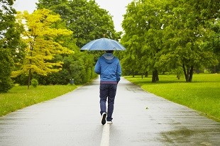 lifespa image, man walking in spring rain with umbrella