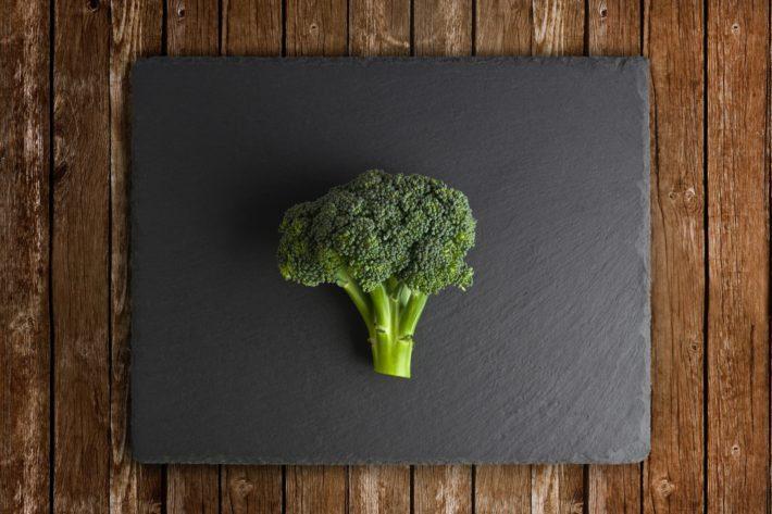 A single stalk of broccoli on a slate cutting board