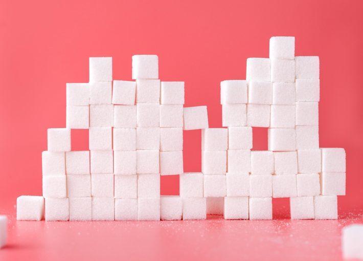 Artful sugar cube sculpture on a pink background