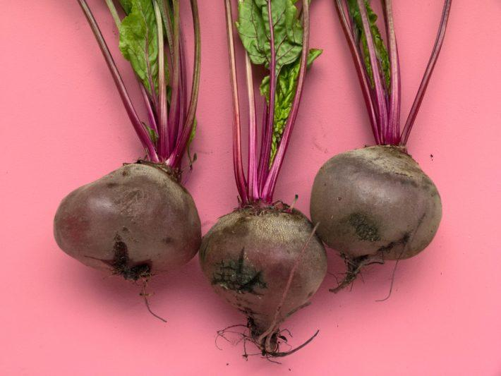 beets with stems and leaves on a pink background