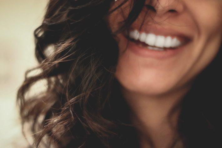 A woman with long brown hair smiles