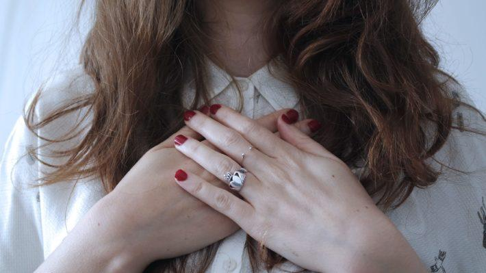 A woman puts her hands over her heart