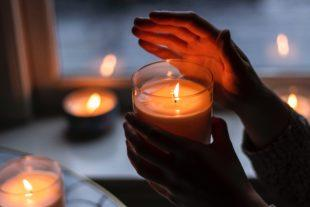 Hands holding a lit candle, in a room full of candles