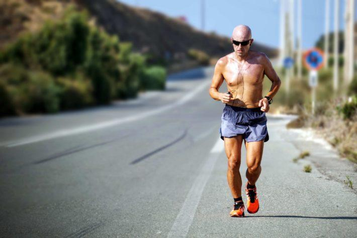 A shirtless, bald man running on a deserted road