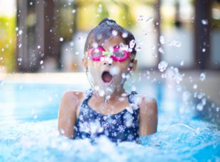 Girl with pink googles taking a breath in a pool before she goes underwater.