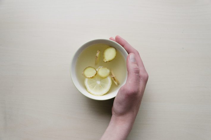 A hand holding a mug of lemon-ginger tea on a white background.
