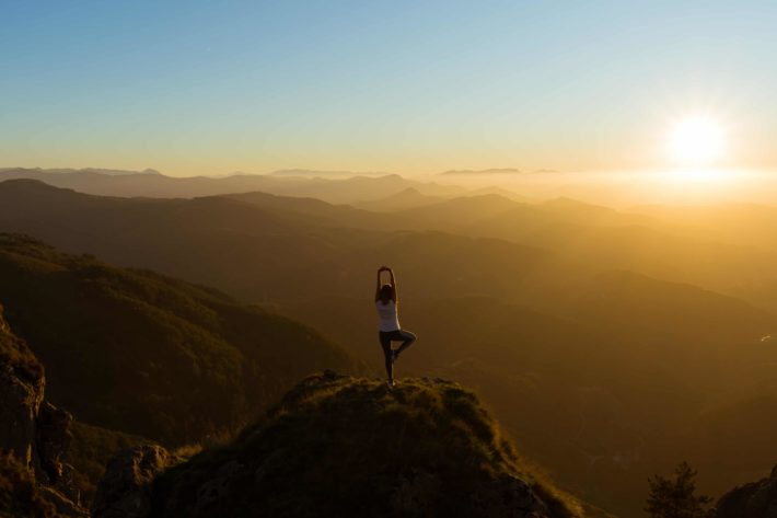 Tree Pose yoga on top of a mountain at sunrise