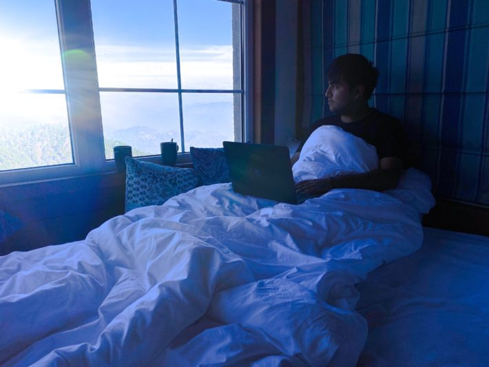 A man in bed with his computer at sunrise looking out the window
