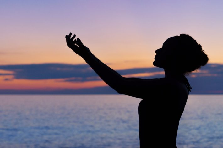 A silhouetted woman holds her hands up in front of the sunset