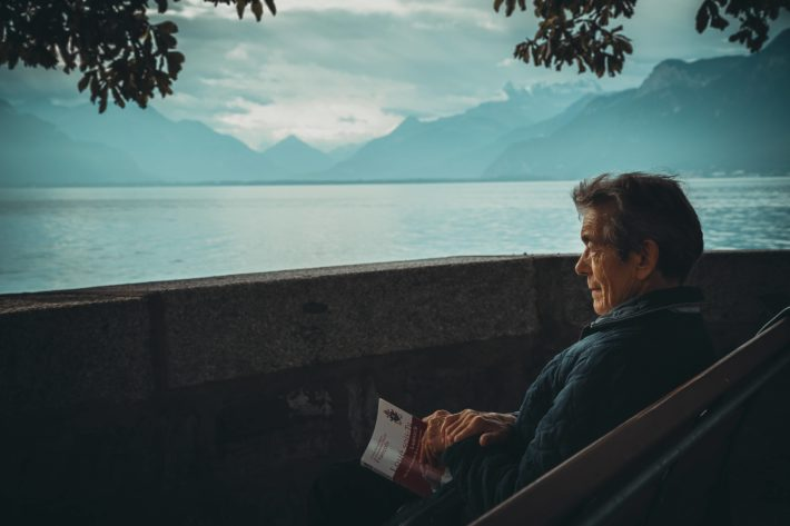 An old man sit reading on a terrace above the sea