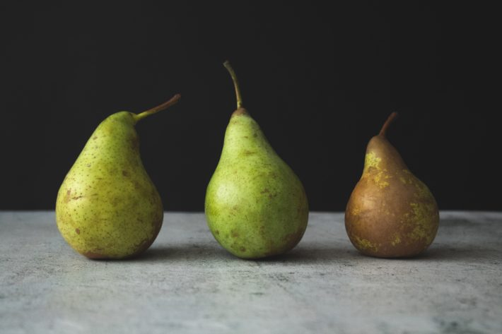 Three green pears, one brown