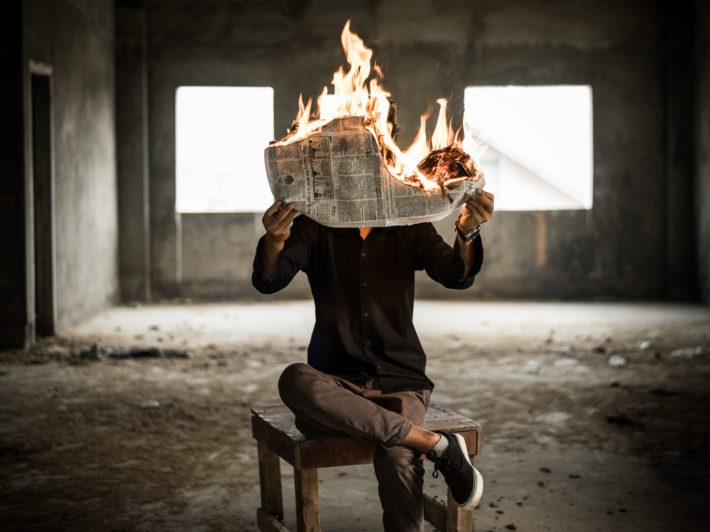 A man reading a burning newspaper