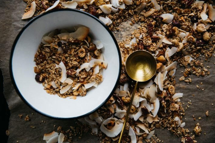 A bowl of granola with a brass scoop