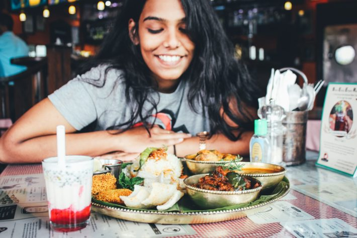 A woman eats Indian food mindfully.