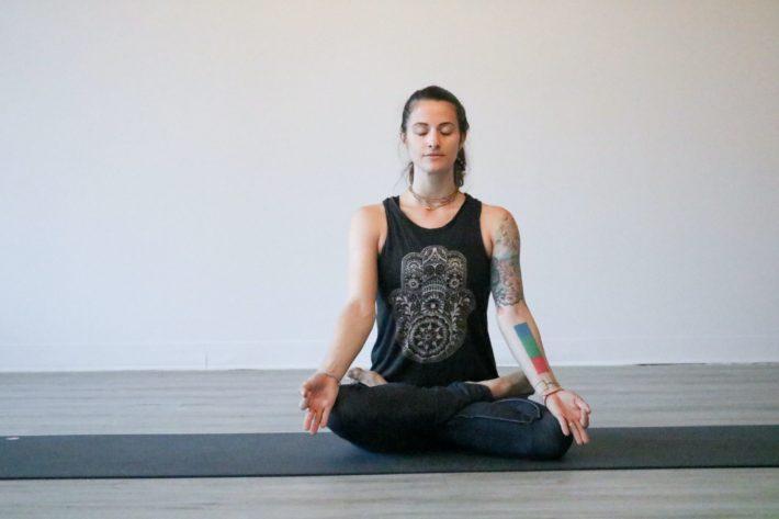 A woman seated in meditation pose practicing pratiloma pranayama