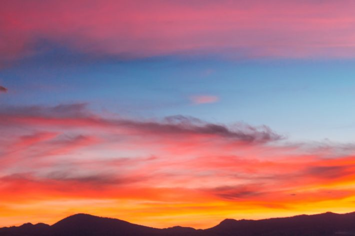 Orange, pink, and blue sunset over the mountains
