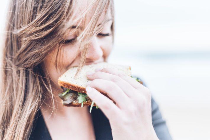 A woman eats a sandwich