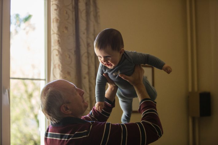 A grandfather holds a baby