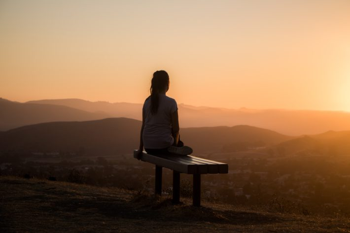 A woman sits on a bench in mediation watching the sunset